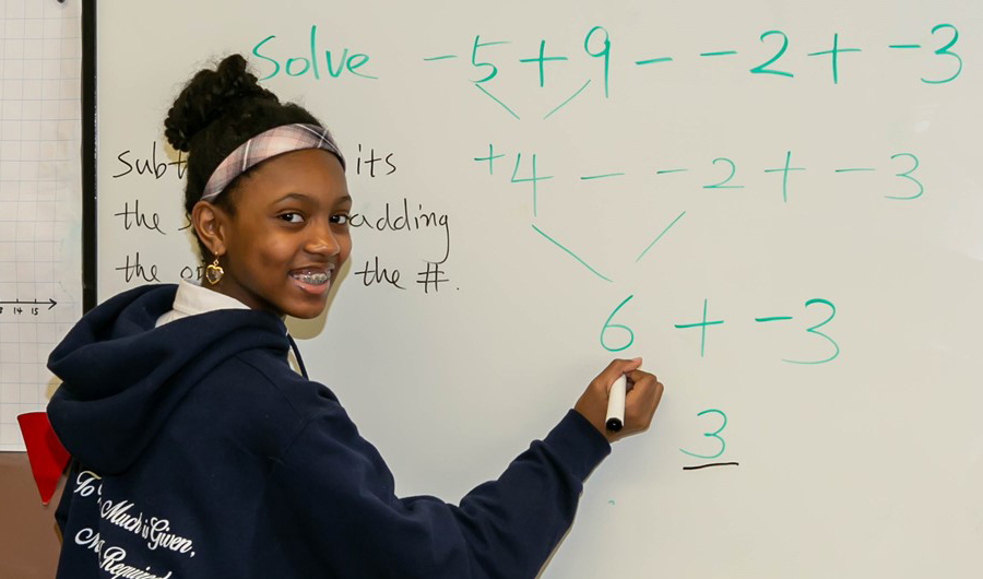 student sharing out math solution on dry erase board