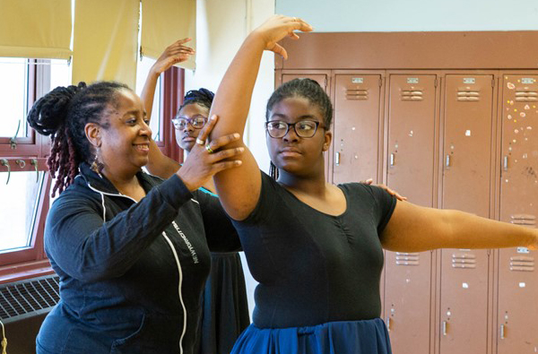 Teacher helping correct student ballet form