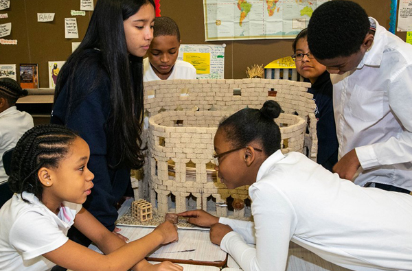 students admiring miniature reconstruction of historical monument